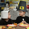 BRYAN EATON/Staff photo. Pilgrims Mackenzie Andrews, 7, and Jarod Nickerson, 8, prepare to dig in to their Thanksgiving Dinner at Salisbury Elementary School. The students in Kelly Clayton and Bethany Marshall's classes have been learning about the beginnings of the holiday and the Wampanoag tribe that met the Pilgrims.