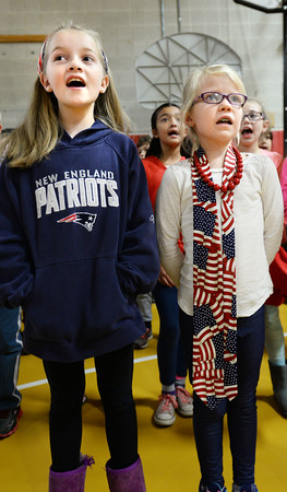 BRYAN EATON/Staff photo. The Cashman School student council held a Veteran's Day Assembly on Thursday with several Viet Nam veterans in attendance. Member of the chorus, including Rebecca Hussey, 8, left, and Carly Testa, 9, lead in the singing of the National Anthem.