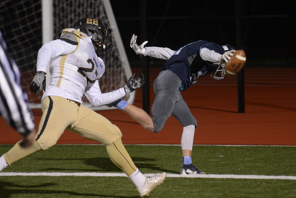 JIM VAIKNORAS/Staff photo Triton's Bryan Hughes scores on a 2 point conversion against  Bishop Fenwick's Isaiah Cashwell- Doel at Triton Friday.