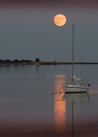 """BRYAN EATON/Staff photo. The """"super moon"""" rises over the Merrimack River on Sunday night with Ben Butler's Toothpick at Salisbury Beach State Reservation underneath. Scores of people were out on the Gillis Bridge and the Newburyport Boardwalk taking photos for the largest image of the moon since 1948."""