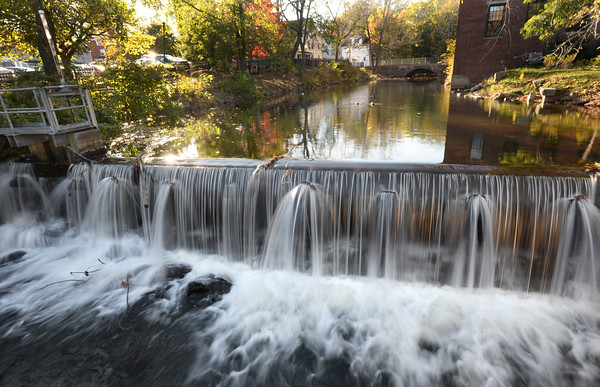 BRYAN EATON/Staff photo. The recent rains have finally caused water to flow over the dam again in Amesbury's Upper Millyard. There had barely been a trickle for much of late summer and fall with the drought.