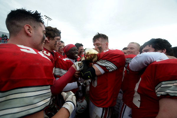 JIM VAIKNORAS/Staff photo Amesbury senion William Parady kisses the Thanksgiving Trophy after defeating Newburyport 22-17 at Landry Stadium in Amesbury Thursday.