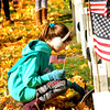 JIM VAIKNORAS/Staff photo Michelle Kilroy, 10 of troop 72309 puts a flag on the grave after the Veterans Day service at Veterans cemetery in Newburyport  Friday . Small flags were pasted out to scouts, both boys and girls, to decortate the graves of veterans.