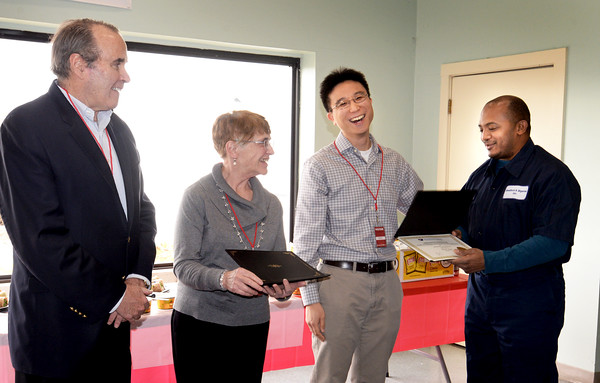 BRYAN EATON/Staff photo. Patrick Liu, an English as a second language instructor at Northern Essex Community College, smiles as Felix Diaz receives his certificate of completion along with 18 others at Bradford and Bigelow in Newburyport's industrial park. Looking on are company president John Galligan, left, and Nancy Tariot, project manager for the program at NECC.