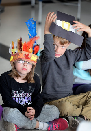 BRYAN EATON/Staff photo. Their headwear may be a little loose-fitting for Ashley Brown, left, and Mason Fowler as they await their Thangsgiving fruit salad on Monday afternoon. The two were among the first-graders at Salisbury Elementary School reenacting the first Thanksgiving.