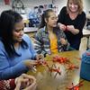 BRYAN EATON/Staff photo. Coastal Connections clients are among those making red ribbons to tie onto automobile antennas for the Amesbury Police Department's new Red Ribbon Campaign For Safety. Coastal Connections' Gisele Khoury works with clients Lucy Cifre, left, and Ashley Oveido making the ribbons.