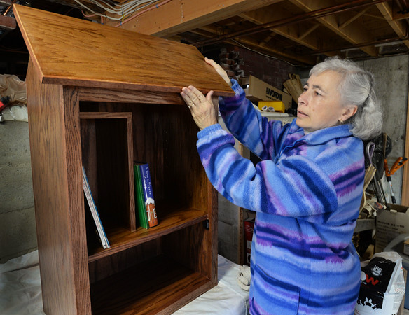 """BRYAN EATON/Staff photo. Katie Johnson's husband Chuck is building a free """"little library"""" outside their Amesbury home at 237 Elm Street at Goss Avenue. Children's books will be a left, with adults to the right, with returns on the bottom."""
