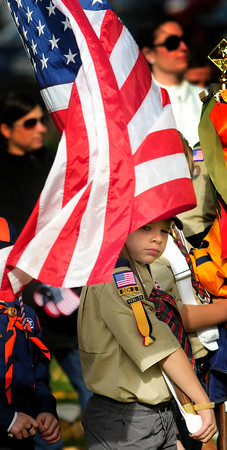 JIM VAIKNORAS/Staff photo Declan Hyer, 9, a member of scout pack 21hold the flag on a windy morning at the Veterans Day service at Veterans cemetary in Newburyport  Friday .