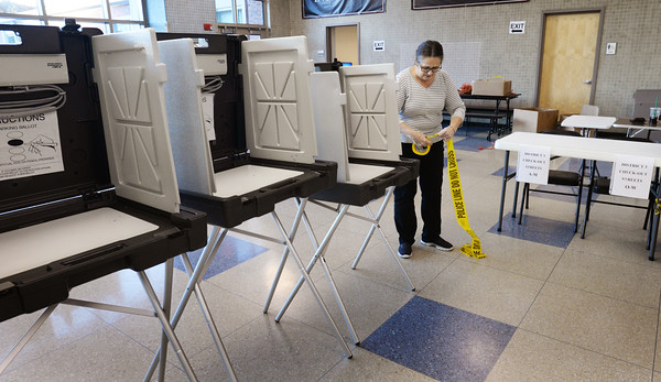 BRYAN EATON/Staff photo. Amesbury city clerk Bonnijo Kitchin puts up police tape between aisles to make sure people deposit their ballots in the right district voting machine. Amesbury's voters head to the high school to cast their ballots Tuesday.