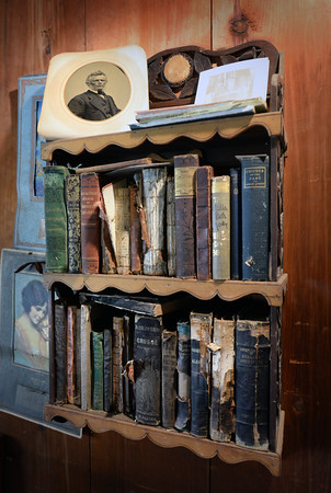 BRYAN EATON/Staff photo. A portrait of one-time Bass-Whitney House owner James Whitney sits atop a collection of books including Robinson Crusoe.