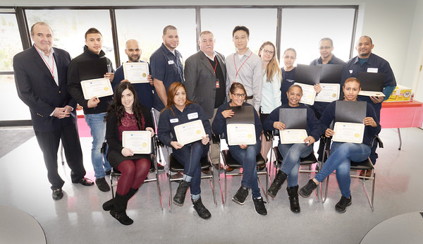 BRYAN EATON/Staff photo. Nineteen employees at Bradford and Bigelow completed an English lanquage course offered through Northern Essex Community College. Those that were on hand Monday pose with company officials after receiving their certificates. Front, from left, Cesiah Albarran Lopez, Andy Maria Rodriguez, Anabel Romero, Virgen Nunez and Fatima Rodriguez. Back, from left, John Galligan, company president; Maximo Rodriguez, Gilbert Rodriguez, Guery Roa, Rick Dunn, executive vice president; Patrick Liu, ESOL Instructor at NECC; Tara Howley, human resources manager;  Gisela Olivero, Jandy Rodriguez and Felix Diaz.