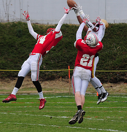 JIM VAIKNORAS/Staff photo Newburyport's Ronnie Mwai goes up to make a reception defended by Amesbury's #14 Logan Burrell and #21 Eric Dawes during  their game at Amesbury Thursday.  Amesbury defeated Newburyport  22-17.