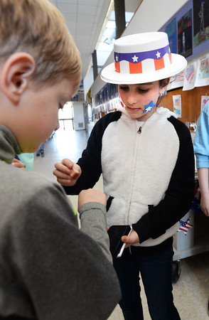 BRYAN EATON/Staff photo. Amesbury's Cashman School student council member Kayleigh Corriveau, 9, stamps Anderson Bolth's hand after he voted in a mock election. The council members, dressed patriotic garb, took each class to the polling booths after they finished lunch on Monday.