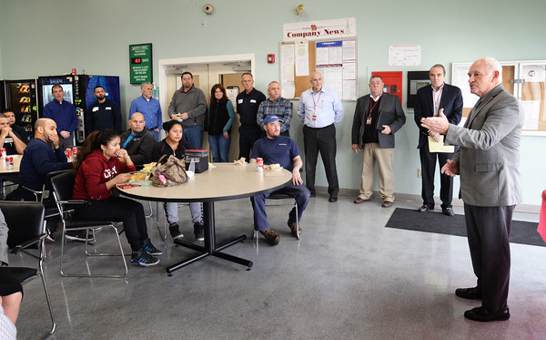 BRYAN EATON/Staff photo. George Moriarty, executive director of corporate and community education at Northern Essex Community College, congratulates employees at the Newburyport printing company Bradford and Bigelow that completed an English language course through the Haverhill-based school.