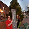 BRYAN EATON/Staff photo. Michelle Lamott, left, and Kate Curry have stepped up as co-chairs of the Amesbury Santa Parade committee, show a seasonal message from Attentif Design, stand in Market Square where the Christmas tree will be lit this weekend.