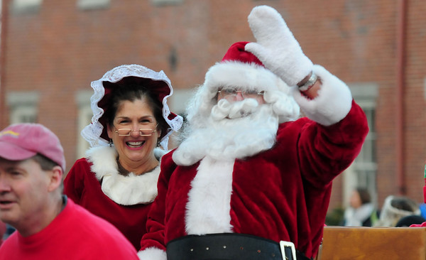 JIM VAIKNORAS/Staff photo Santa and Mrs Claus ride in the Rotary Club sleigh on their way to the annual tree lighting in Market Square In Newburyport Sunday.
