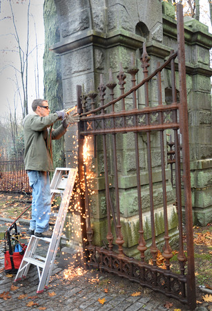 BRYAN EATON/Staff photo. After a 156 years, the removal of the bolts to the gates took some doing with a blowtorch, lubricants and pounding a rod into the holes with a sledgehammer.