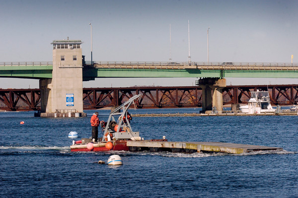 BRYAN EATON/Staff photo. Even though Monday's weather was seasonally warm, it's no doubt that boating season is over as evidenced by boatyard crews taking docks out of the Merrimack River for the season.