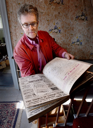 BRYAN EATON/Staff photo. Dan Meader looks through a guest ledger from 1897 Newburyport's Wolfe Tavern which was demolished in 1954.