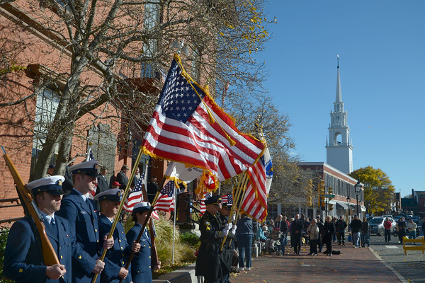 JIM VAIKNORAS/Staff photo Members of the US Coast Guard and the Newburyport Police Dept hold tight to their flags during a windy Veterans Day service at Newburyport City Hall Friday .