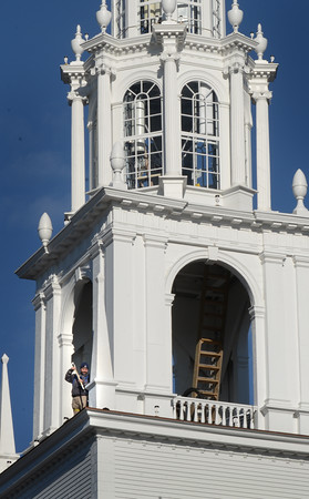 BRYAN EATON/Staff photo. A worker from American Steeple, based in Salem, paints sections of the Unitarian Church, which went through extensive repairs and renovations, in downtown Newburyport on Friday. The weekend looks good for outdoor activities, including painting, with sun in the forecast and the temperature in the mid-50's.