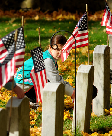 JIM VAIKNORAS/Staff photo Emma Cowles, 11,  of troop 85332 puts a flag on the grave after the Veterans Day service at Veterans cemetery in Newburyport  Friday . Small flags were pasted out to scouts, both boys and girls, to decortate the graves of veterans.