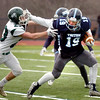 BRYAN EATON/Staff photo. Triton's Lewi L'Heureux goes for yards holding off Pentucket's Chris Muollo.