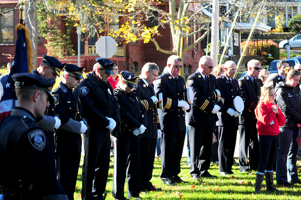 JIM VAIKNORAS/Staff photo Amesbury emergency police and firefighters bow their heads during the benediction at Amesbury Middle School during the annual service Friday.