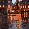 BRYAN EATON/Staff photo. The Christmas Tree in Newburyport's Market Square reflects in puddles Tuesday afternoon. It doesn't look like snow will cover the tree any time soon as temperatures are going to rise a little.