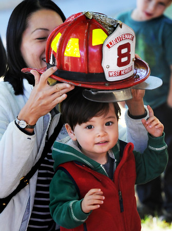 BRYAN EATON/Staff Photo. Caili Kimball puts a West Newbury firefighter helmet on her son Oliver Kimball-Nisbert, 2, of Newburyport at the G.A.R. Memorial Library in West Newbury. The children were at safety day and got to check out a police cruiser and fire engine and see different equipment.