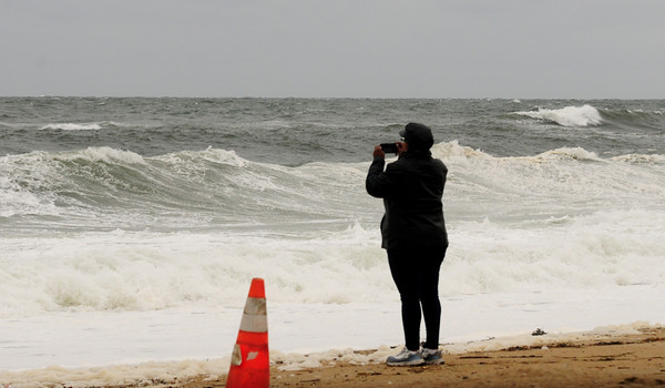 JIM VAIKNORAS/Staff photo A woman use her phone to photograph the high surf off Salisbury Beach Friday afternoon.