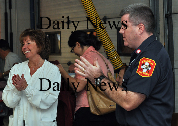 Salisbury - Amesbury firefighter Dave Mather and nurse Cathy Vichill sanitize their hands in between giving H1N1 vaccines to the long line of people with reservations at Salisbury Fire Station on Wednesday evening.  Brett Languirand/Staff photo