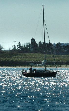 Newburyport: A sailboats heads up the Merrimack River under motor power Monday afternoon, the Plum Island Lighthouse visible in the back. Bryan Eaton/Staff Photo