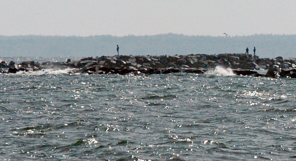 Salisbury: A couple people made it out to the north jetty of the Merrimack River in a view from the end of Atlantic Avenue at Salisbury Beach on Wednesday. Several people reported seeing a whale swimming in the area. Bryan Eaton/Staff Photo