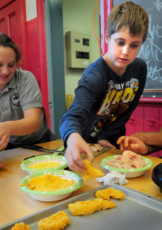 Newburyport: Jack Bryk, 11, dips chicken into an eggwash and then ground cereal as he make Cap'n Crunch chicken. He was a the Kelley School Youth Center where they have a cooking class once a month. Bryan Eaton/Staff Photo