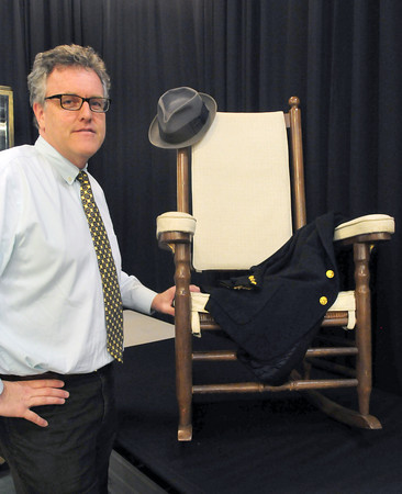 """Amesbury: Auctioneer Dan Meader with """"rocker II"""" that President John F. Kennedy used on Cape Cod along with a cashmere jacket made for him in 1961 and a fedora hat worn by the slain president. Bryan Eaton/Staff Photo"""