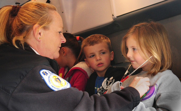 """Newburyport: Chloe Raby, 6, listens to her heartbeat with a stethoscope as a crew with Atlantic Ambulance Service visited the Brown School in Newburyport on Thursday. It was part of their """"Safety in the Community"""" program where they get acguainted with the different agencies including fire and police. Bryan Eaton/Staff Photo"""