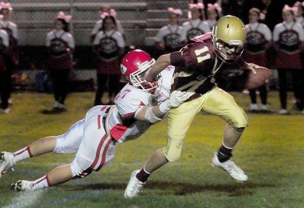Newburyport: Newburyport quarterback Michael Shay throws off Masconemet's Mackenzie Cashin to make a pass which was incomplete. Bryan Eaton/Staff Photo