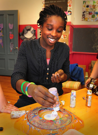 """Newburyport: Mary Osazuwa, 11, drops paint onto a spinning piece of paper as she creates """"spin art."""" She was in the art room at the Kelley School Youth Center in Newburyport on Monday afternoon. Bryan Eaton/Staff Photo"""