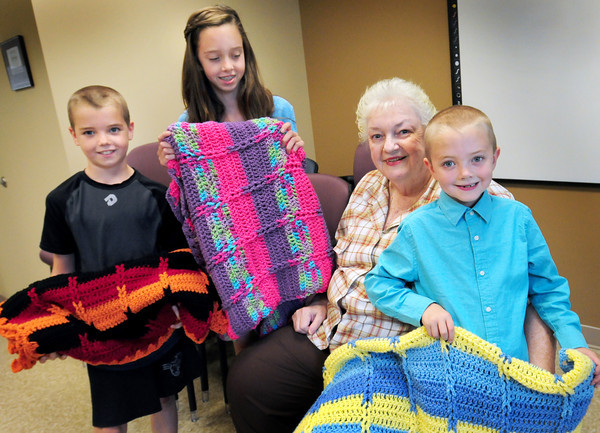 Amesbury: Amesbury resident Jane Tierney's grandneice and nephews from Newburyport have seen her crotchet blankets for Blankets For Kids for a number of years that are donated to children in need through the Amesbury Council on Aging and this year the children bought yarn with money they had recieved as gifts. Presenting the blankets to the council from left, Owen, 10, and Lindsey Roberts, 12, Jane Tierney and Theo Roberts, 6. Bryan Eaton/Staff Photo