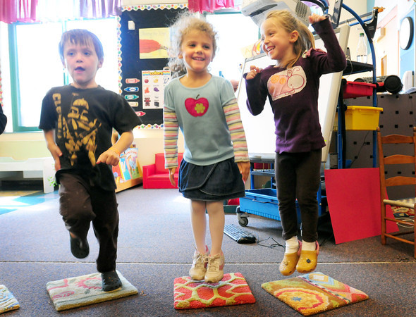 """Newbury: Twins Charlie Shanley, left, and Kiera, right, with Izzy Vadala, all 4, dance to the """"Funky Chicken"""" in Mary Jo Lagana's pre-kindergarten class at Newbury Elementary School. The younsters were getting some excercise before their afternoon snack on Tuesday. Bryan Eaton/Staff Photo"""