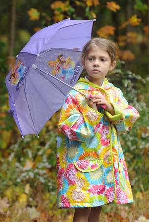 west Newbury: Sophia Bellacqua, 4, keeps dry as she watches the Apple Harvest Road Race in West Newbury with her family Sunday. Jim Vaiknoras/staff photo