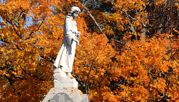 Newburyport:A statue at the grave marked Nevins in St Mary's Cemetery in Newburyport stand in front of the brilliant colors of fall early Sunday morning. Jim Vaiknoras/staff photo
