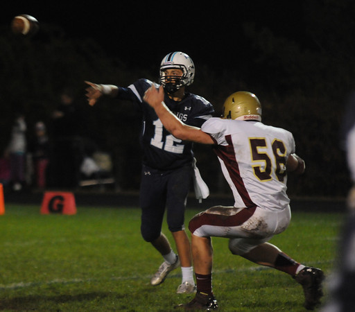 Byfield: Triton Quarterback Bradly Whitman gets off a pass under pressure from Newburyport's Dillon Guthro during their game at Triton Friday night. Jim Vaiknoras/staff photo