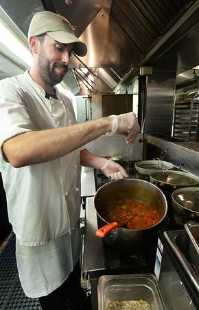 BRYAN EATON/ Staff Photo. Matt Bradley adds some spice to the chili at the Grog Restaurant.