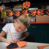 "BRYAN EATON/ Staff Photo. Taylor Pappas, 8, creates a jack-o-lantern in Linda Greenfield's art class at the Cashman School in Amesbury on Monday like the ones behind her. The students were learning about symmetric balance making one half of the image ""negative"" and the other, ""positive."""