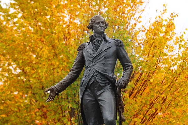 JIM VAIKNORAS/Staff photo The George Washingto statue at the Bartlet Mall in Newburyport seems to be welcoming the colorfull fall foliage behind it on a cloudy Saturday morning.