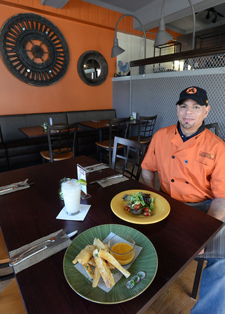 BRYAN EATON/Staff photo. Chef Elvis Jimenez-Chavez, shown with yucca fries and a a roasted avocado salad, plans to open his Coop Rotisserie this weekend in downtown Amesbury.