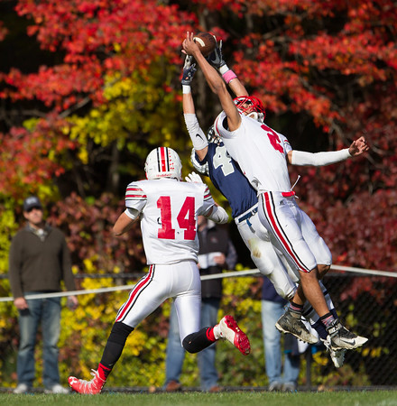 Jared Charney / Photo Amesbury's Zachary Levarity goes high to break up a pass play to Hamilton-Wenham's Cam Peach at Hamilton-Wenham High School, Saturday, October 15, 2016.