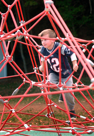 BRYAN EATON/Staff photo. Ty Masiello, 5, climbs up the spider web in the playground at the Bresnahan School on Monday during recess. The weather was perfect for outdoor activities and should continue until Wednesday.